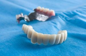 A front shot of a set of dentures resting ion a blue clloth